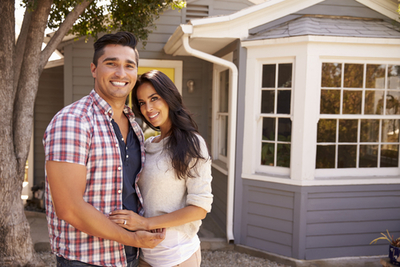 Man and Woman In Front of Suburban Home