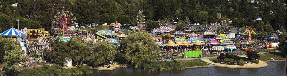 Panaramic view of a county fair from a distance. Visible are tents and carnival rides.