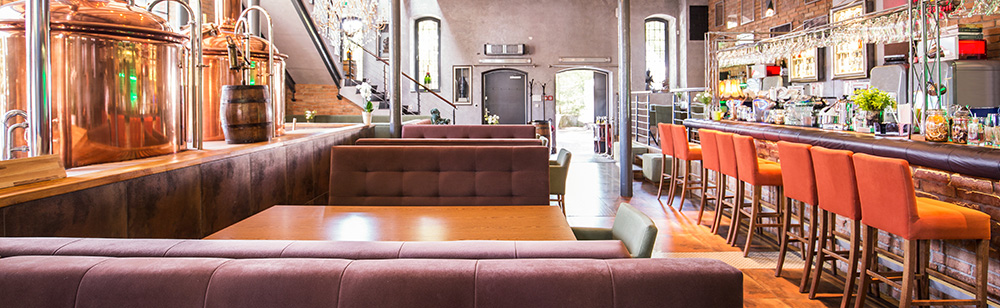 Inside a microbrewery with brown leather booths and orange upholstered bar stools up at the counter.
