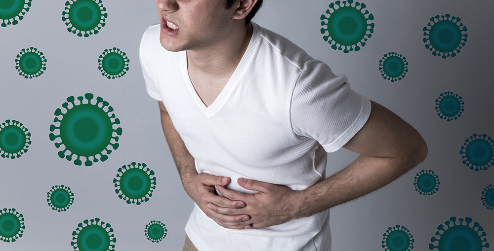 Image of man clutching his stomach as if he were sick. Background has green illness-causing bacteria.