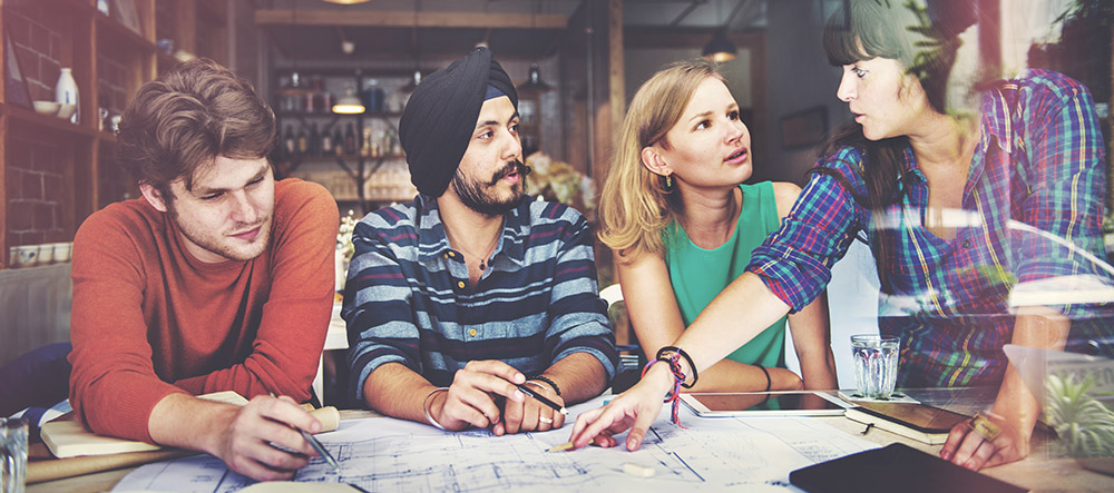 Image of 4 people at a table inside a restaurant reviewing blue prints.