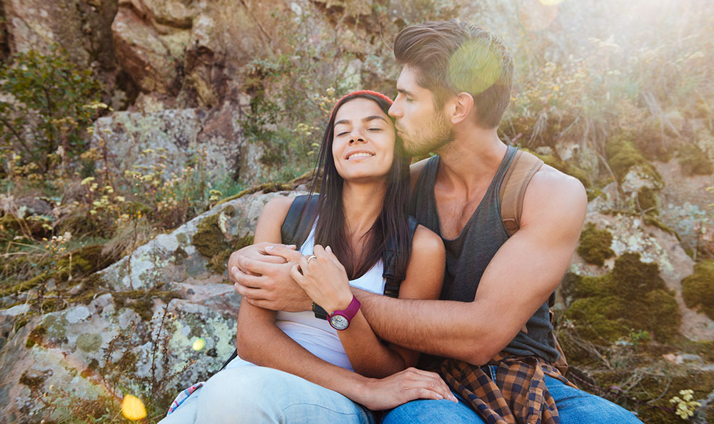 Young Latino couple sitting on a mountain. His arms are around her and he's kissing her on the head.